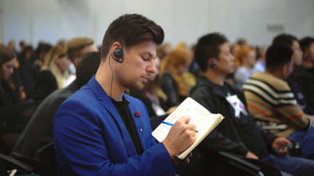 Crowd student study forum business man auditorium college. Education audience person write note. Studying crowded seminar writing notepad. Auditorium group people listen educational speech high school 写真素材