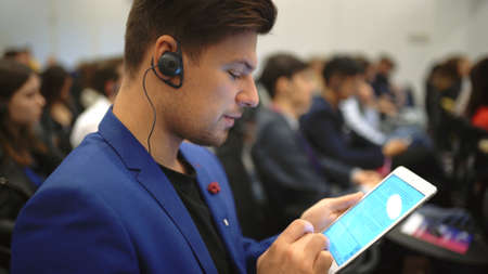 Person type touch screen crowded audience business forum. Viewer conference listen speaker auditorium. Business man typing hand pad economic summit. Group people learning speech in crowd audience. 写真素材