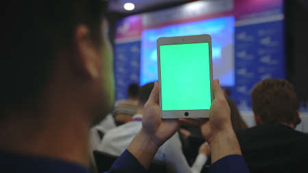 Touch screen pad on forum business meet. Audience conference with notepad. Keying mockup video. Key green screen tablet business man. Auditotium people seminar with touching device. Replace cut photo.