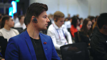 Audience business meet crowded forum person. Viewer conference listen headphone speaker auditorium. Event economic summit business man spectator. Group people listening translate speech crowd audience 写真素材