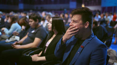 Person yawn at business meet boring lecture speaker. Crowded audience asleep. Expressive face sleeping business man on forum. People emotion yawning at conference. Auditorium sleep tired from insomnia