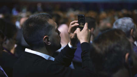 Person take photo on phone in crowded audience business forum. Conference business man with mobile. Seminar for viewer auditorium. group people listen speaker speech. Taking photography scene on phone 写真素材
