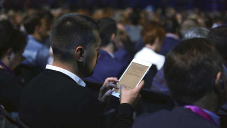 Crowded students study conference business man audience college. Education auditorium person typing touch pad. Studying crowd type text touching screen. Audience group people listen educational speech 写真素材 - 158502861