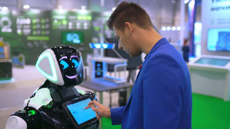 People like for first time learning data base robot clicking on touch screen machine close up. Cyborg help human with education library digital information. Man in suit tries click on android display. 写真素材