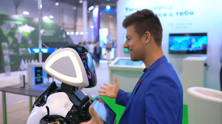 People in suit hugs robot loving closeup of greeting new friend 4K. An artificial intelligence bionic organism learn human behavior. A man enjoy hugging a tech cyborg for the friendship of the future.