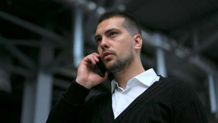 Successful white collar business man standing and talking on phone closeup with serious face 4K. Business people speaking on mobile with partners. Manager stand and talk on phone with work colleagues.