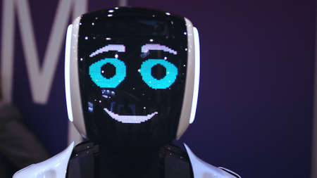 Beautiful portrait robot pulse heart on digital display pixel smile closeup looking at camera 4K. design sweet cyborg demonstrate 8 bit love. heart beat smiling android with feeling loving for people. 写真素材
