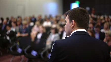 Speaker business meet talk audience from stage in microphone. Presenter economic forum speak public. Educational speech business man. Speaker talking group people at convention. Presentation men.