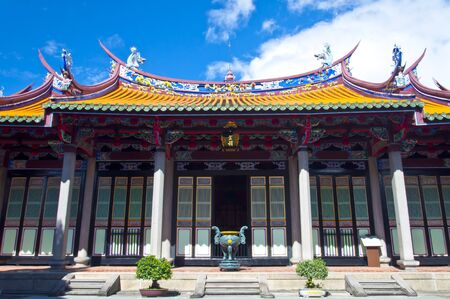 confucian: Taiwan Asian outdoor temple cultural totem carving wood yellow red white blue sky background Confucian temple Stock Photo