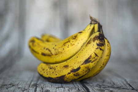 Wood background with overripe bananas