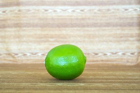spoilage: green lemon put on wooden table Stock Photo