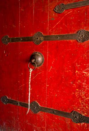 Red vintage door embellished with round brass Standard-Bild