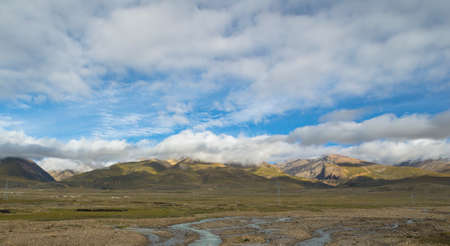 Snowy mountains and grassland under blue sky and white clouds