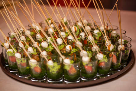 Canapes of quail egg, cheese, vegetables on the tray. Close-up