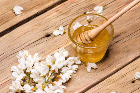 honey with acacia blossoms on a wooden background.