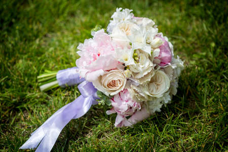 Wedding bouquet of purple and white flowers lying on grass