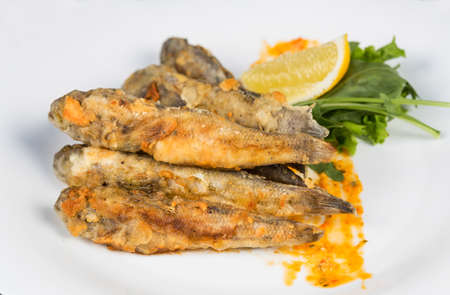 Fried fish gobies in batter with lemon and greens