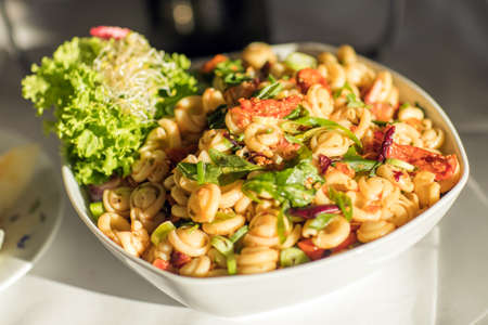Pasta with fresh vegetables on white plate