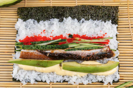 Making Rolled Sushi in a bamboo Sushi Mat Imagens