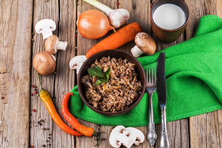 Buckwheat porridge with mushrooms in the frying pan on the table