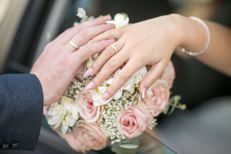 Couples hands wearing their wedding rings resting on the wedding bouqet