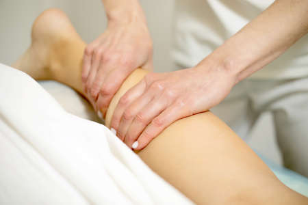 Sports Massage. Massage therapist working with patient, massaging his calves.