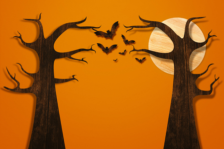 Halloween and decoration concept. Bats flying and tree made from wood on orange brick wall Stock Photo