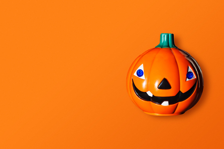 Halloween and decoration concept. Pumpkins made from wood on orange background. Top view and copy space