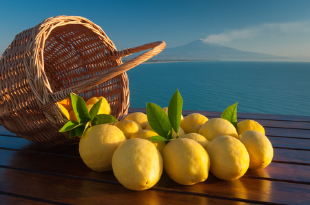 Wicker basket full of  lemons on a wooden table with blue sea and mount Etna in the background