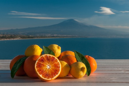 Oranges and lemons on a wooden table with blue sea, Mount Etna and clouds in the background Фото со стока