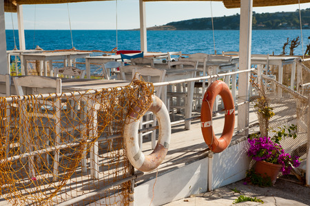i net: View of a rustic sea restaurant i with two life belts and a fishing net in the foreground