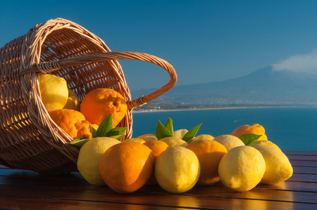 Wicker basket full of lemons and oranges on a wooden table with blue sea and mount Etna in the background photo