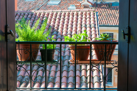 An open window with a typical balcony of northern Italy and some flowered vases Stock Photo