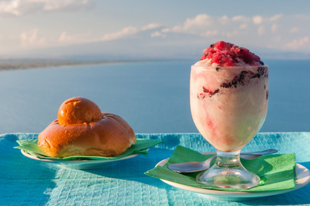 Glass of sicilian granita and a typical warm brioche with sea and mount etna in the background Stock Photo