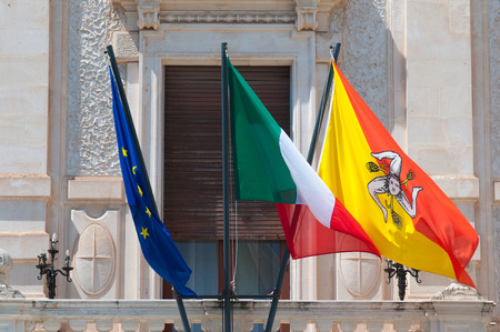 syracuse: Flags of Europe, Italy and Sicily waving all together in a balcony in Syracuse