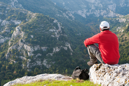 Hiker sitting on the rocky edge of one of Pantalica,s canyons in Sicily photo