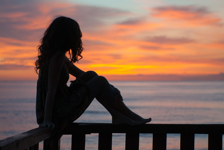 young woman sitting on a balcony by the sea and waiting the sunrise Stock Photo