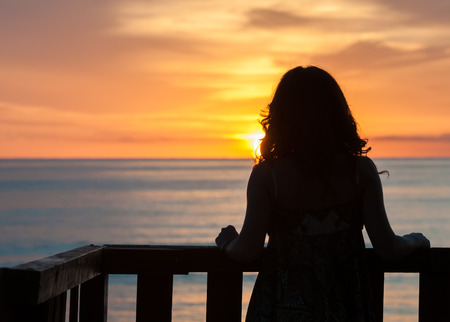 Girl seen from behind standing on a balcony in front of the sea and looking the sunrise Фото со стока - 34365888