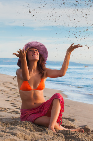 Joyful girl sitting by the sea and throwing sand in the air