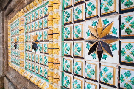 Close-up view of a eight point star and of typical colored tiles from Caltagirone used  as ornament along one of the main street of the town