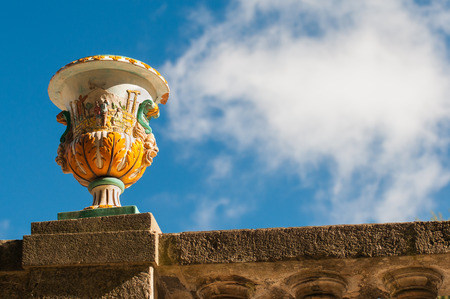 View of a colored ceramic vase from Caltagirone used as an ornament in the main public gardens of the town with blue sky and clouds in the background