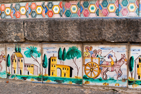 Close-up view of some steps of Caltagirone staircase with colored ceramic tiles portraying the characteristic sicilian cart Фото со стока
