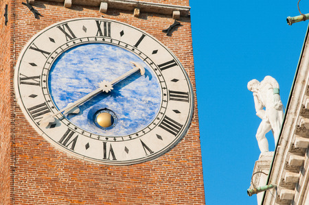 zoomed in: Zoomed view of the clock of BIssara tower in Vicenza and one of the statues placed on the roof of the Palladian Basilica