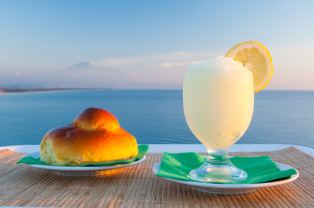 Sicilian lemon granita and a typical warm brioche with blue sea and Mount Etna in the background photo