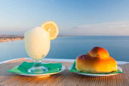 Sicilian lemon granita and a typical warm brioche with blue sea and Mount etna in the background Stok Fotoğraf - 35966509