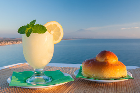 sicilian: Sicilian lemon granita and a typical warm brioche with blue sea and Mount etna in the background