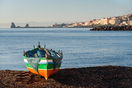 Fishing boat in a beach near the town Acitrezza, Eastsicly, with its houses and typical lava stacks in the distance Stock Photo