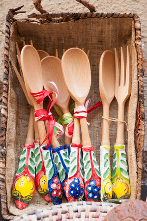 folkloristic: View of some wooden spoons and forks with ceramic decorations, souvenirs along the streets of Taormina
