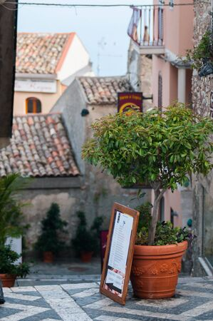 Perspective of a flowered vase along one street in the small village of Castelmola and some roofs of its typical houses photo