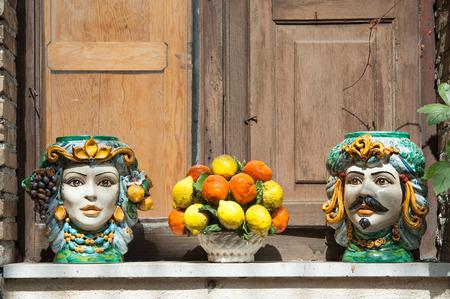 Vasi in ceramica tipici e oggetti di artigianato siciliano utilizzati come ornamenti su un davanzale della finestra a Castelmola, Sicilia Archivio Fotografico